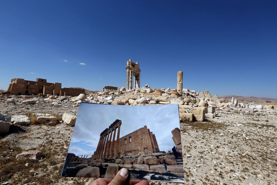 A general view taken on March 31, 2016 shows a photographer holding his picture of the Temple of Bel taken on March 14, 2014 in front of the remains of the historic temple after it was destroyed by Islamic State (IS) group jihadists in September 2015 in the ancient Syrian city of Palmyra. Syrian troops backed by Russian forces recaptured Palmyra on March 27, 2016, after a fierce offensive to rescue the city from jihadists who view the UNESCO-listed site's magnificent ruins as idolatrous. / AFP / JOSEPH EID (Photo credit should read JOSEPH EID/AFP/Getty Images)
