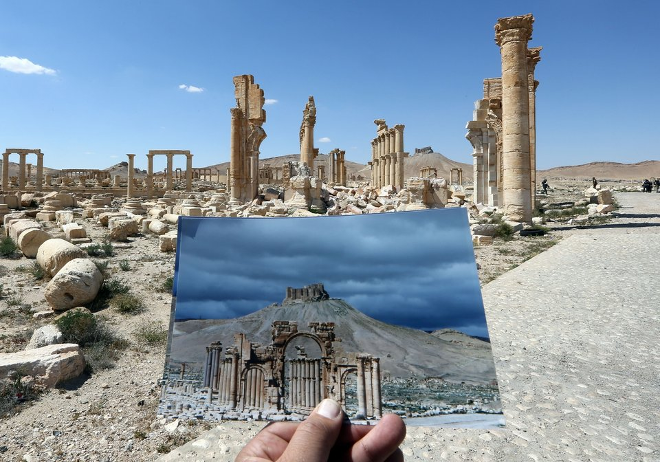 A general view taken on March 31, 2016 shows a photographer holding his picture of the Arc du Triomphe (Triumph's Arch) taken on March 14, 2014 in front of the remains of the historic monument after it was destroyed by Islamic State (IS) group jihadists in October 2015 in the ancient Syrian city of Palmyra. Syrian troops backed by Russian forces recaptured Palmyra on March 27, 2016, after a fierce offensive to rescue the city from jihadists who view the UNESCO-listed site's magnificent ruins as idolatrous. / AFP / JOSEPH EID (Photo credit should read JOSEPH EID/AFP/Getty Images)